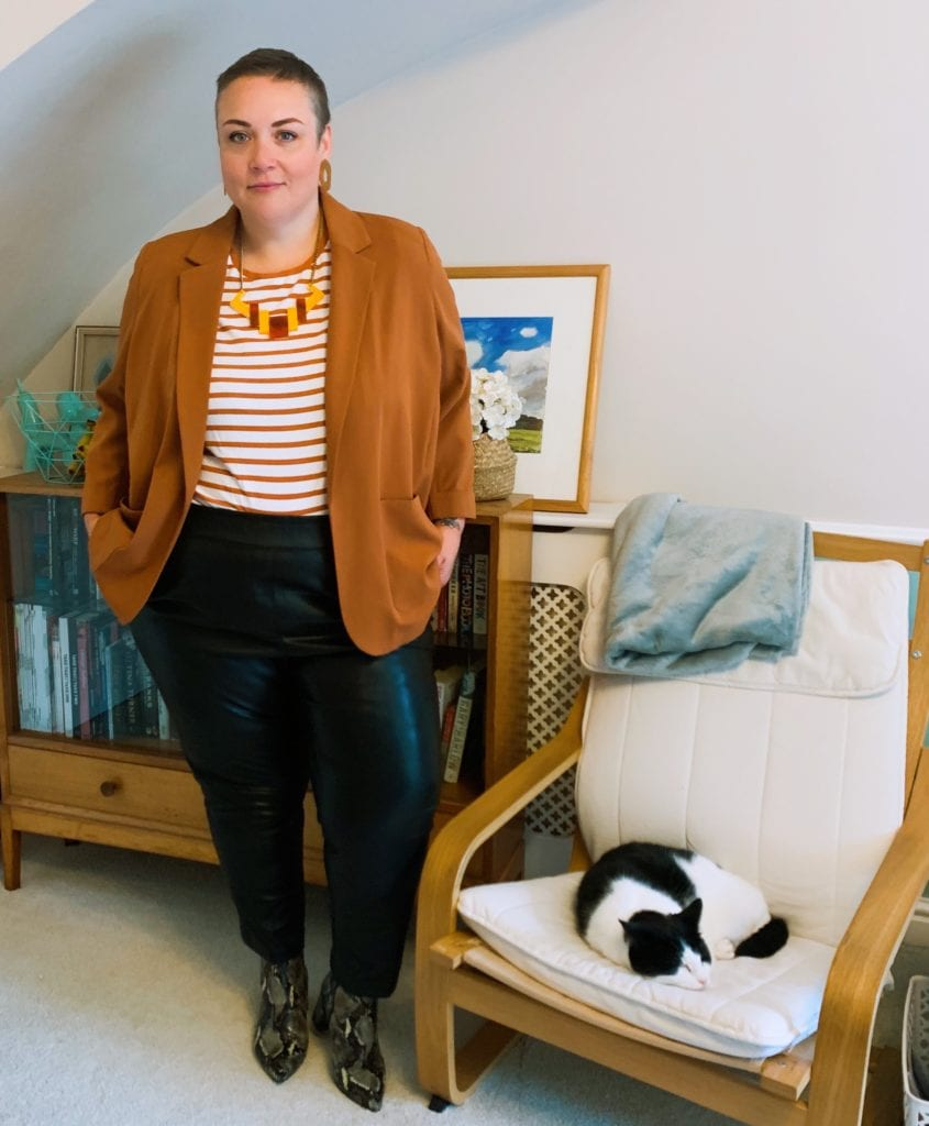 Becky wears a blazer and striped tee with pleather trousers
