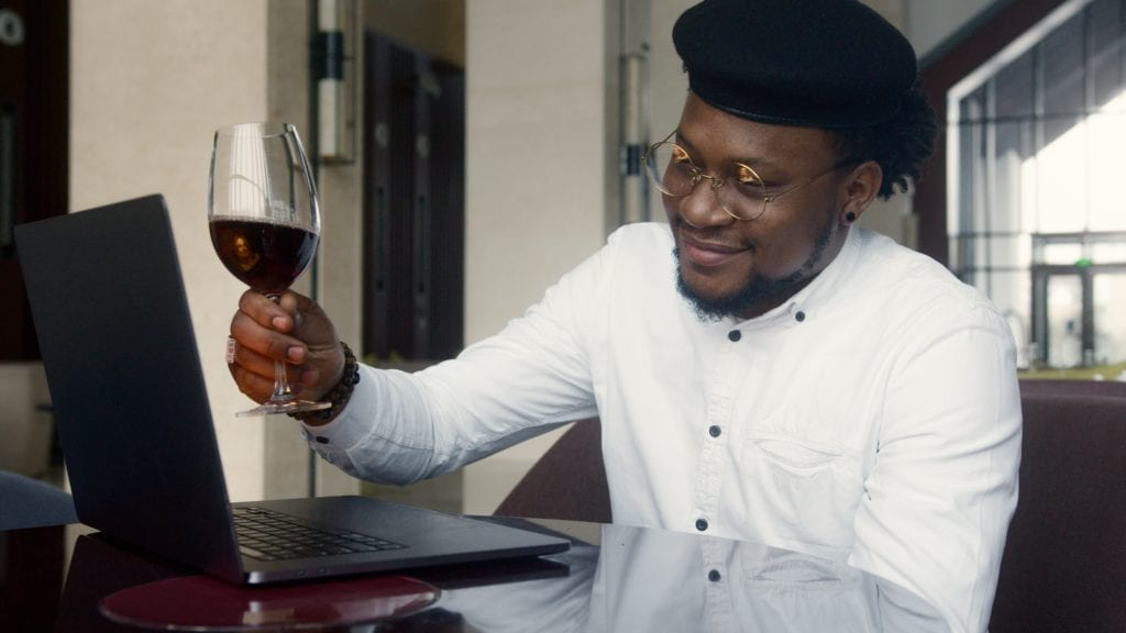 A black man holds a glass of wine while on an online date with laptop