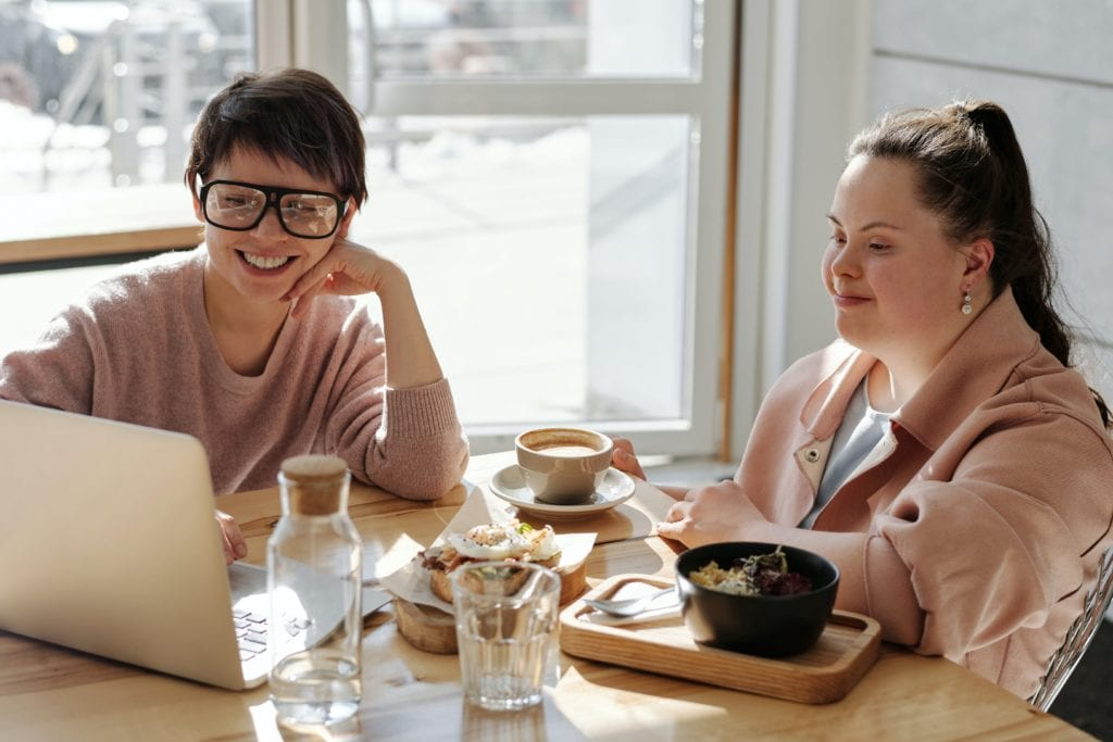 Two young women are sat in a cafe. One of the women has down syndrome.